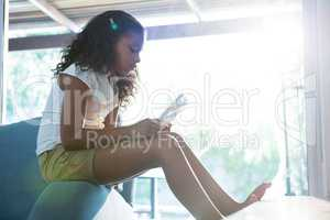 Side view of girl using tablet while sitting on armchair