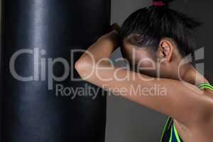 Exhausted female boxer leaning on punching bag
