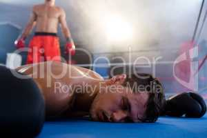Unconscious male boxer lying by athlete in ring