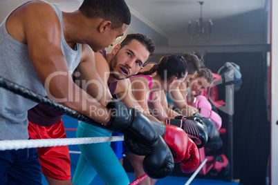 Tired male and female boxers leaning on rope
