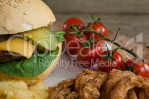 Hamburger, onion ring, cherry tomato and french fries on chopping board