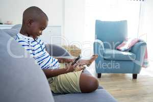 Side view of boy using mobile phone while sitting on sofa