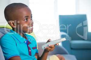 Smiling boy holding remote control on sofa at home