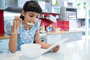 Girl eating breakfast while looking at digital tablet
