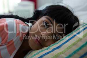 Close-up portrait of girl lying on bed