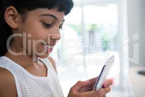 Close-up of girl texting from mobile phone in kitchen