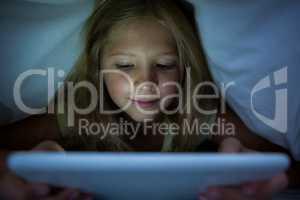 Girl using tablet computer under blanket