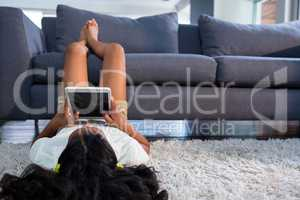 Girl using digital tablet while lying on rug