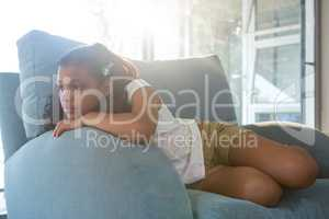 Thoughtful girl leaning on armchair