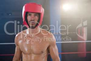 Portrait of shirtless male boxer wearing red headgear