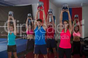 Young athletes lifting kettles by boxing ring