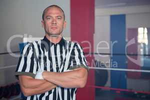 Portrait of male referee standing in with arms crossed