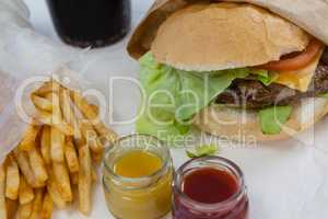 Close-up of hamburger, french fries, sauce and cold drink