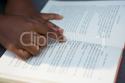 Hands of boy pointing at book