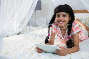 Smiling girl using digital tablet on bed at home