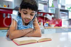 Girl reading novel with arms crossed in kitchen