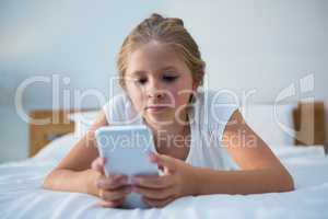 Close up of girl using smartphone on bed