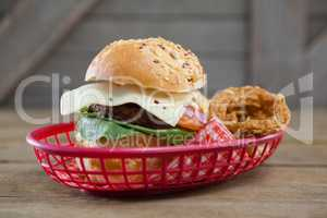 Hamburger and onion rings in basket