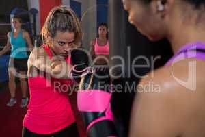 Athlete holding bag while female boxer punching