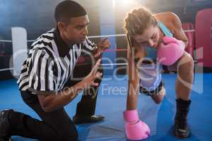 Referee gesturing to female boxer in ring