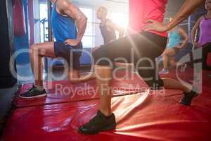 Back lit athletes practicing lunge exercise on mats