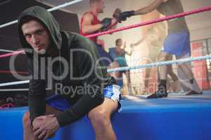 Portrait of young male boxer sitting on boxing ring at fitness studio