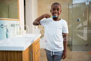 Portrait of smiling boy with toothbrush by sink