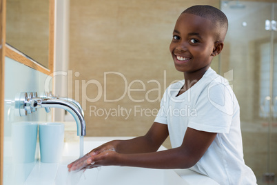 Portrait of smiling boy washing hands in sink