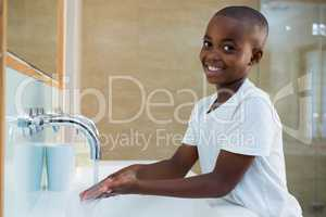 Portrait of smiling boy washing hands in sink