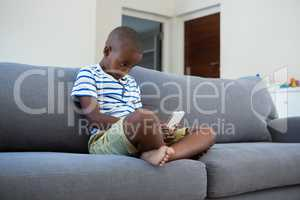 Boy using mobile phone sitting on sofa at home