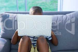 Boy sitting on sofa while using laptop against window at home