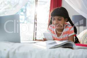 Girl using mobile phone while lying by book and laptop on bed