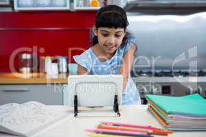 Smiling girl using digital tablet amidst colored pencils and books