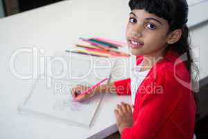 High angle portrait of girl drawing in book