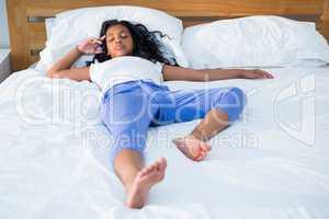 Full length of girl sleeping in bed