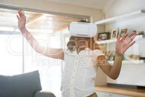 Cheerful girl wearing virtual reality simulator while standing in living room