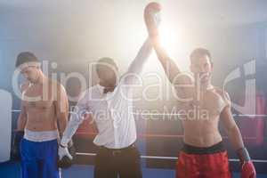 Referee lighting hand of winner in boxing ring
