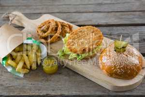 High angle view of burger with onion rings and french fries