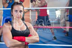 Portrait of confident female boxer standing with arms crossed