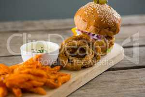 Close up of hamburger by onion rings with dip and french fries