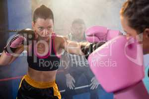 Female athletes fighting in boxing ring