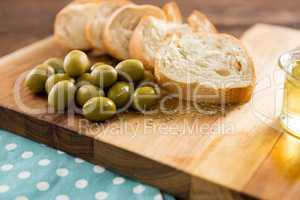 Olive oil with olive and bread kept on chopping board