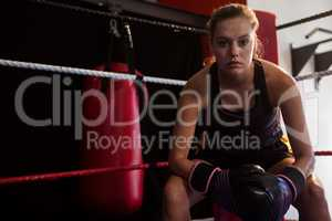 Portrait of confident woman sitting in boxing ring