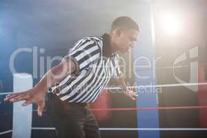 Young male referee showing hand sign in boxing ring