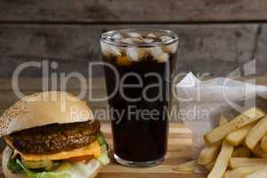 Hamburger, french fries and cold drink on table