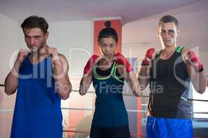 Portrait of confident female amidst male boxers standing in fighting stance