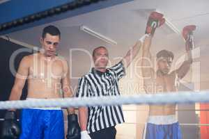 Referee holding hands of winning male boxer by athlete