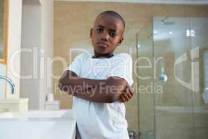 Portrait of boy standing by sink with arms crossed