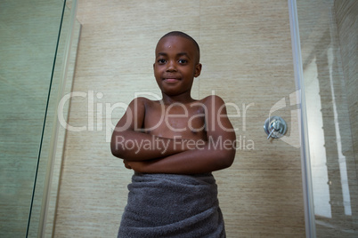 Low angle portrait of shirtless boy wrapped in towel standing with arms crossed amidst glass