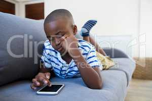 Bored boy lying on sofa while using mobile phone at home